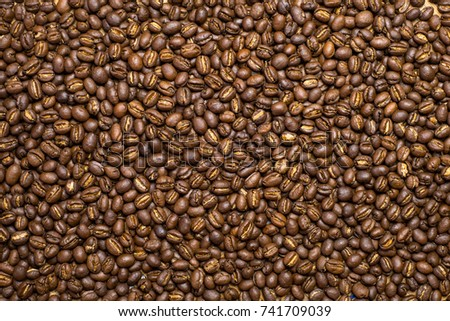 Medium dark Roasted peaberry coffee beans background.  #741709039
