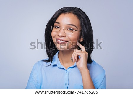 Pleasant woman in glasses touching her cheek with finger #741786205