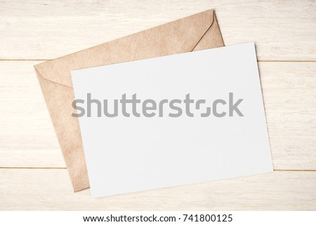 Blank white card and envelope on wooden table Royalty-Free Stock Photo #741800125