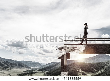 Businessman walking blindfolded on concrete bridge with huge gap as symbol of hidden threats and risks. Skyscape and nature view on background. 3D rendering. #741885559