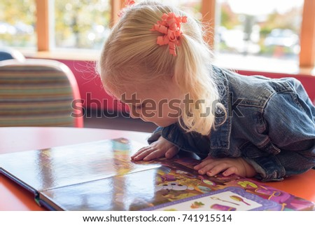 Little preschool girl fully engaged in a picture book at the public library