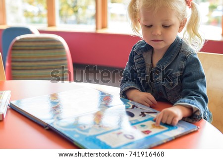 Little girl looking at a picture book at the public library on a sunny day