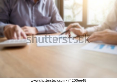 Blurred of Business team two executive discussing and analysis working Financial investment on calculator with calculate on tablet Analyze business and market growth on financial document data graph. #742006648