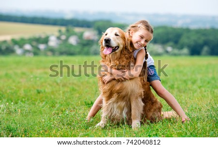 Cute smiling Little girl hugging retriever in the summer park Royalty-Free Stock Photo #742040812