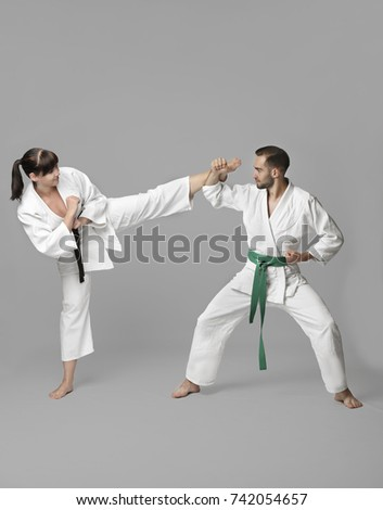 Young man and woman practicing karate on light background #742054657