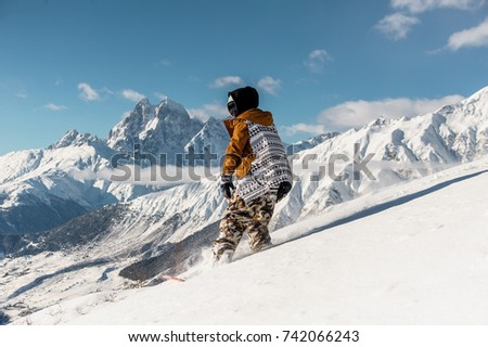 Portrait of female snowboarder in sportswear riding on the mountain slope against the scenic background of mountains #742066243