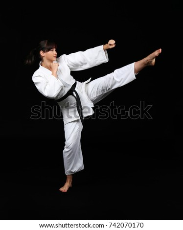 Young woman practicing karate on dark background #742070170
