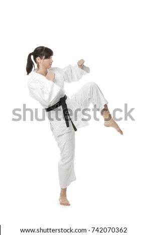 Young woman practicing karate on white background #742070362