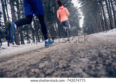 Young couple running outdoors in the winter.