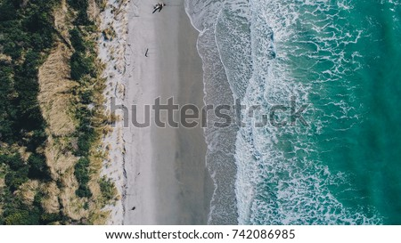 Beach on aerial drone top view with ocean waves reaching shore, op view aerial photo from flying drone of an amazingly beautiful sea landscape . #742086985