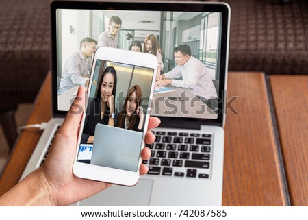 Hand holding the technology smart mobile phone having video conference via monitor display for working in the Loft cafe workplace, entrepreneur business and technology concept #742087585