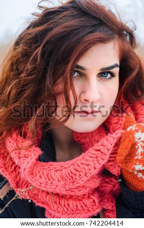 a young girl walks in the field. Dressed in winter clothes, she has blue eyes and thick red hair . Hair curls , the color of fire . #742204414