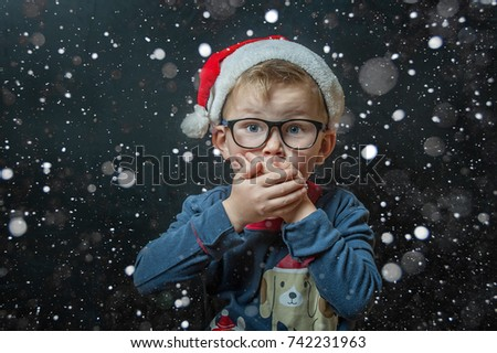 Christmas magic. Little boy covering his mouth with hands. Happy xmas and New Year. Portrait of shocked and surprised child in Santa red hat