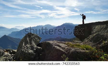 OROBIE MOUNTAINS, ITALY - CIRCA AUGUST 2017:  a hiker stands on a big boulder in the Orobie mountains and admires the beauty of  nature. #742310563