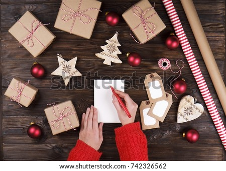 Female hand writing a letter to Santa on wooden background with christmas gifts top view #742326562