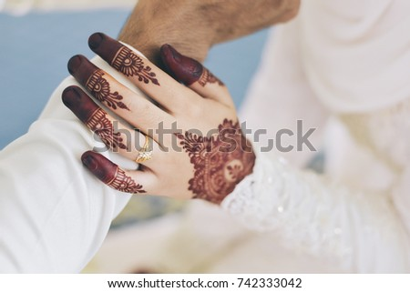 diamond ring on a bride hand with henna (malaysian bride and groom) - wedding concept #742333042