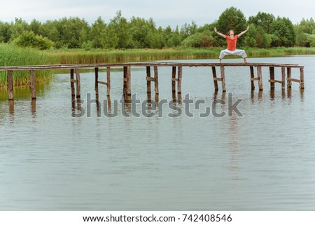 A man doing yoga on wooden pier at the lake #742408546