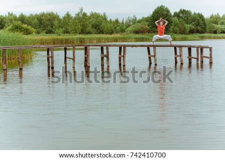 A man doing yoga on wooden pier at the lake #742410700