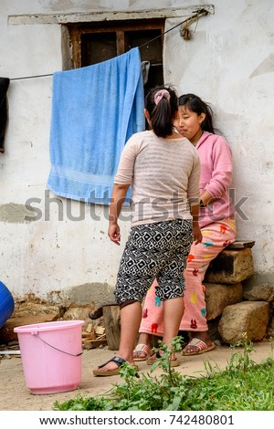 TRIMPHU, BHUTAN - MAR 8, 2017: Unidentified Ngalops women talk about something near the house. Ngalops is one of the most populous ethnic groups of Bhutan #742480801