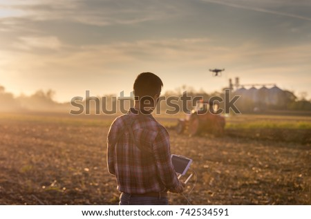 Attractive farmer navigating drone above farmland with silos and tractor in background. High technology innovations for increasing productivity in agriculture Royalty-Free Stock Photo #742534591