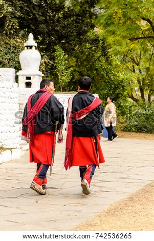 TRIMPHU, BHUTAN - MAR 8, 2017: Unidentified Ngalops men in traditional clothes walk on the street. Ngalops is one of the most populous ethnic groups of Bhutan #742536265