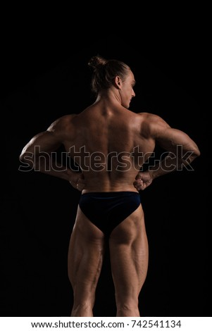 Male athlete bodybuilder posing on a black background #742541134
