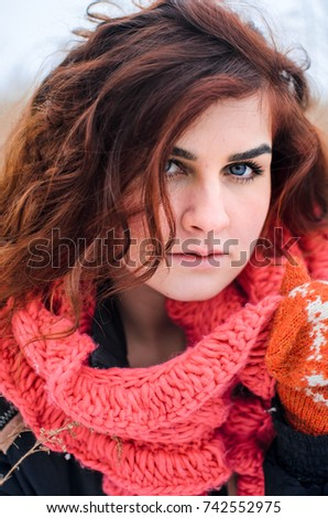 a young girl walks in the field. Dressed in winter clothes, she has blue eyes and thick red hair . Hair curls , the color of fire . orange gloves #742552975