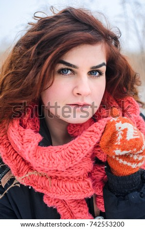a young girl walks in the field. Dressed in winter clothes, she has blue eyes and thick red hair . Hair curls , the color of fire . orange gloves #742553200