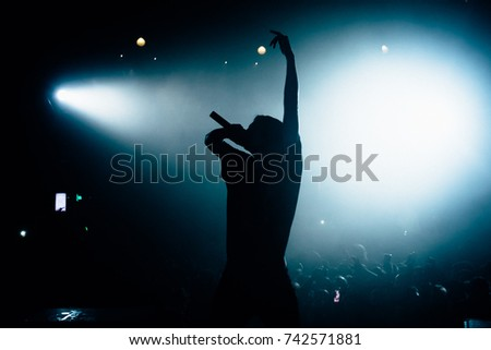 Silhouette of singer rising his hand opposite stage crowd. Floodlights lightning at the camera. Beautiful pool of white light on the background. #742571881
