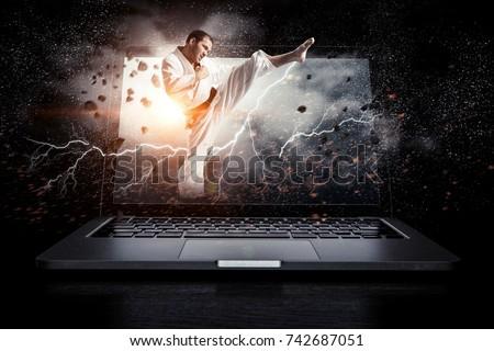 Man in kimono and glowing laptop. Mixed media Royalty-Free Stock Photo #742687051