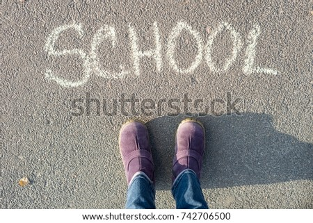 The word school on the asphalt and the feet of the student. Back to school #742706500