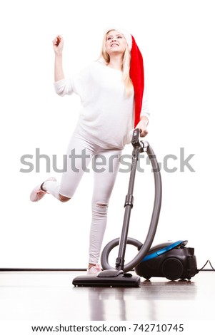 Woman vacuuming the house. Funny teen girl in santa helper hat with vacuum cleaner. Christmas time and housework concept. #742710745