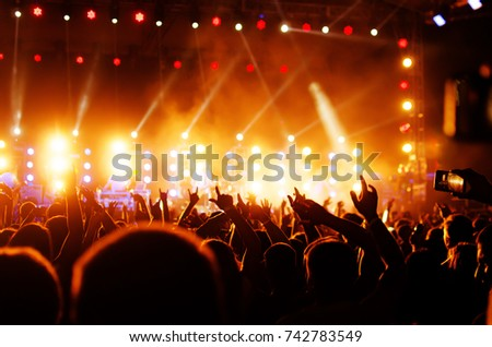 silhouettes of concert crowd and mohawk punk hair style in front of bright stage lights #742783549