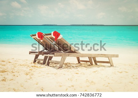 Christmas at the beach - chair lounges with Santa hats at sea #742836772