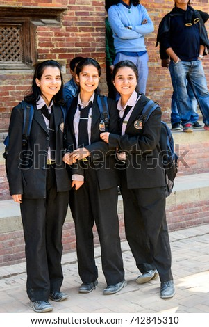 KATMANDU, NEPAL - MAR 6, 2017: Unidentified Chhetri three girls in suits with backpacks smile. Chhetris is the most populous ethnic group of Nepal #742845310