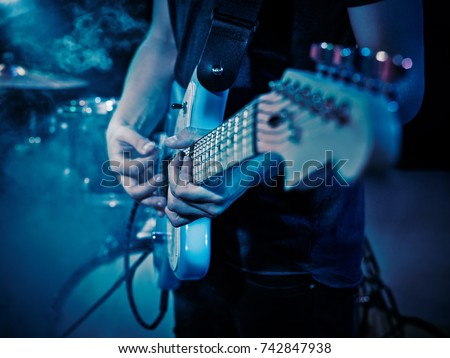 Performance of the rock band. The guitarist plays solo. The bass player plays solo. Drummer. Bass drum. Close-up. #742847938