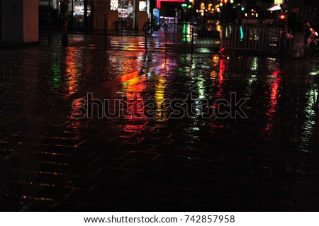 Colorful neon light reflections on cobblestone street scene in Paris.  Dark and rainy evening in city. Horizontal photo with copy space. #742857958