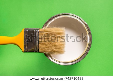 Brush and paint can on green background #742910683