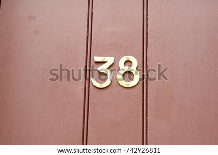 House number 38 sign on red painted door #742926811