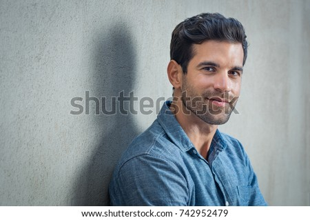 Handsome young man posing on grey background. Portrait of satisfied businessman against grey wall. Close up face of fashionable latin man on grey background. Royalty-Free Stock Photo #742952479