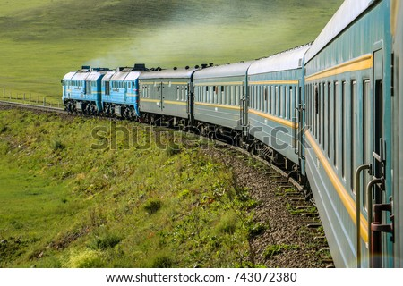 Transsiberian Railway with locomotive and steam crossing through Mongolia on a sunny summer day (near Ulaanbaatar, Mongolia, Asia) Royalty-Free Stock Photo #743072380