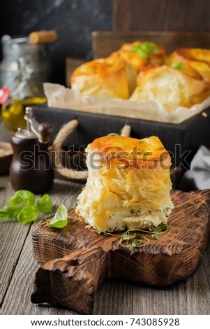 Buns with feta cheese and basil of yeast dough on a dark wooden background. Selective focus. Rustic style. #743085928
