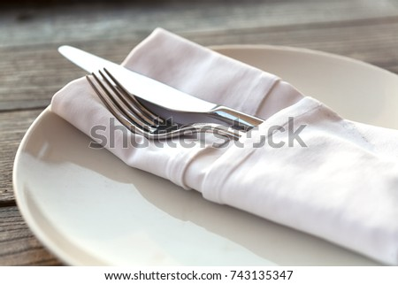 Utensils or cutlery neatly wrapped in a white napkin and served on a simple white plate   #743135347