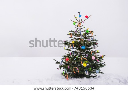 curious open air christmas tree in the snow decorated with sausages, balloons, toilet brushes and clothespins #743158534