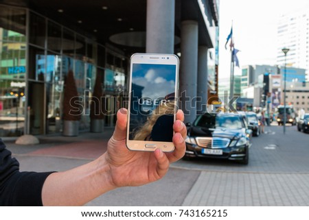 Tallin, Estonia - August, 2017: The Uber company's logo is displayed on the Samsung smartphone screen. Street of the city with cars in the background. #743165215