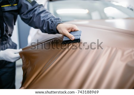 Car wrapping specialist putting vinyl foil or film on car. Selective focus. Royalty-Free Stock Photo #743188969