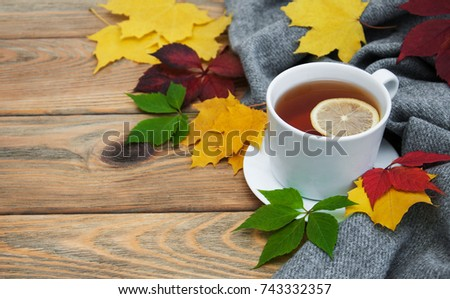 Cup of tea and autumn leaves on a old wooden table #743332357