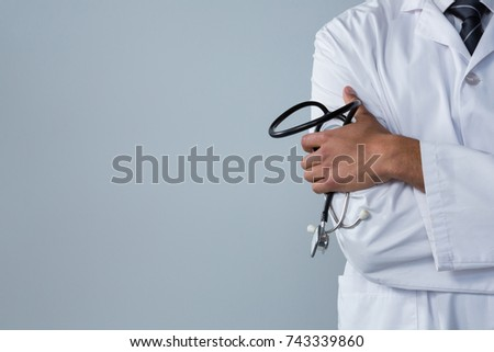 Mid section of doctor holding a stethoscope against white background #743339860