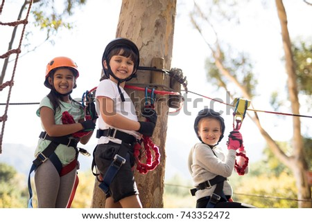 Happy kids enjoying zip line adventure on sunny day #743352472