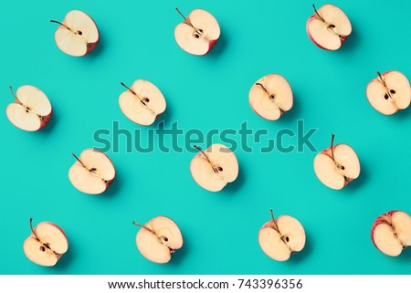Colorful fruit pattern of fresh apple halves on blue background. From top view